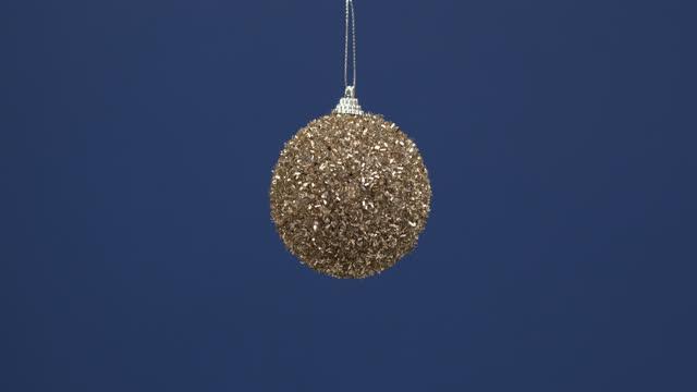 weihnachten glitzernde dekoration für den neujahrsbaum hängen auf einem blauen hintergrund. - exklusiv stock-videos und b-roll-filmmaterial