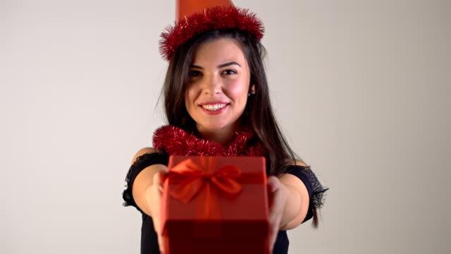 4k hält weihnachten glücklich lächelnde junge frau geschenkbox in händen. - weihnachtsmütze stock-videos und b-roll-filmmaterial