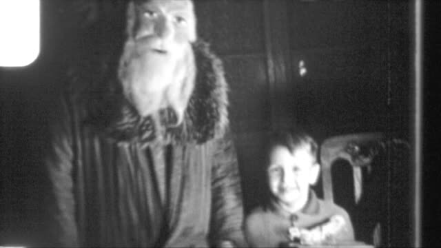 vidéos et rushes de christmas in a family in berlin in times of war santa claus with a young boy boy playing with model railway german soldier in uniform and his son... - wehrmacht