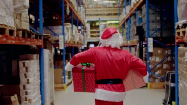christmas in a warehouse. santa claus carrying christmas gifts - christmas gift stock videos & royalty-free footage