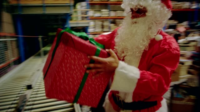 christmas in a warehouse. santa claus carrying christmas gifts - christmas present stock videos and b-roll footage