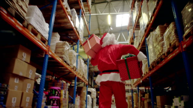 Christmas in a warehouse. Santa claus carrying christmas gifts