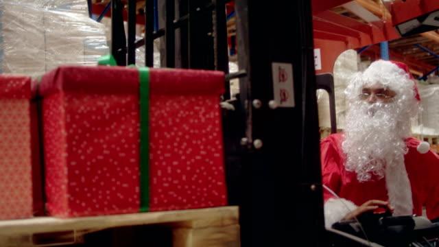 vidéos et rushes de noël dans un entrepôt. santa claus, ramasser les cadeaux de noël avec chariot élévateur - faire fonctionner