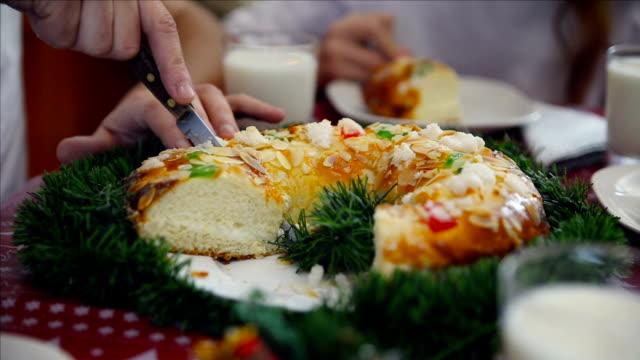 vídeos y material grabado en eventos de stock de christmas in family. close-up of a delicious roscón de reyes while being cut by a hand - reyes magos