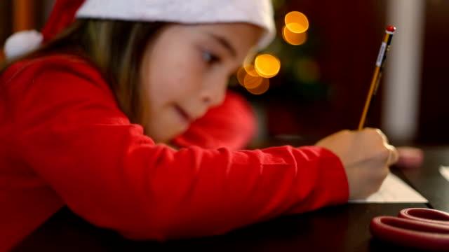 vídeos de stock e filmes b-roll de christmas in spain. adorable little girl giving her best to write the letter to santa claus - correio