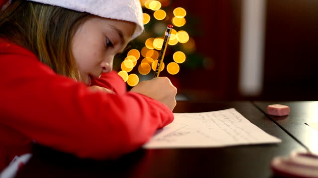 Christmas in Spain. Adorable little girl giving her best to write the letter to Santa Claus.