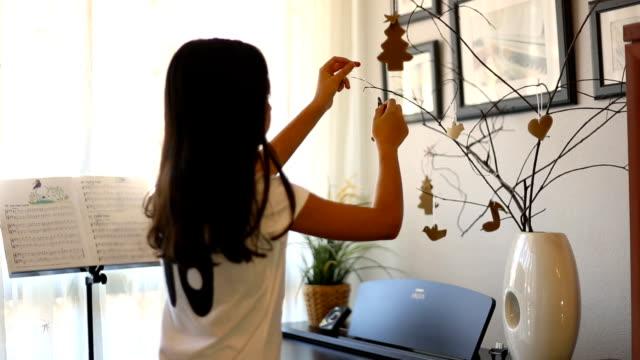 christmas in spain. brunette latin girl decorating a modern minimalist christmas tree. - nur mädchen stock-videos und b-roll-filmmaterial
