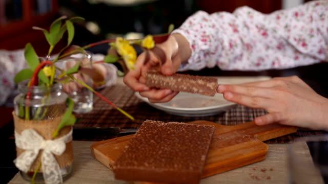 vídeos y material grabado en eventos de stock de christmas in spain. girl's hands cutting a chocolate nougat and giving a piece to her sister - golosina