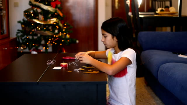 christmas in spain. latin brunette girl doing crafts to decorate her house on christmas. - auf dem boden sitzen stock-videos und b-roll-filmmaterial