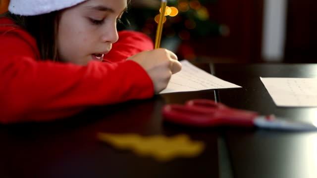 vídeos y material grabado en eventos de stock de christmas in spain. little girl eith santa claus hat giving her best to write the letter to santa claus. - reyes magos