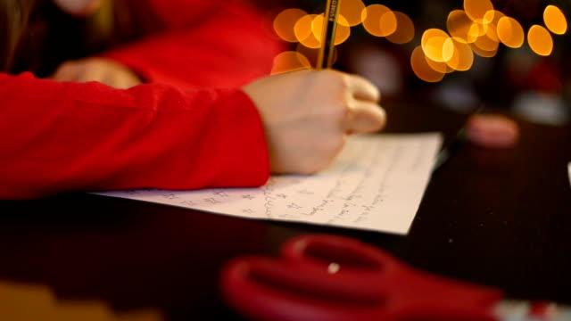 vídeos y material grabado en eventos de stock de christmas in spain. little girl writing the letter to santa claus (or the three wise men) at home - reyes magos