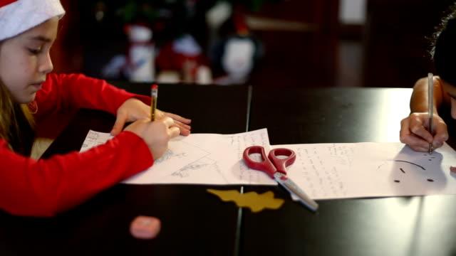 vídeos y material grabado en eventos de stock de christmas in spain. two sisters writing the letter to santa claus (or the three wise men) at home - reyes magos