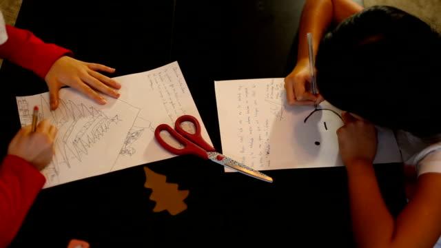 vídeos y material grabado en eventos de stock de christmas in spain.two sisters writing the letter to santa claus (or the three wise men) at home - reyes magos