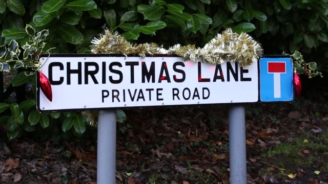 christmas lane road sign decorated with baubles, holly and tinsel, cumbria, uk. - tinsel stock videos & royalty-free footage