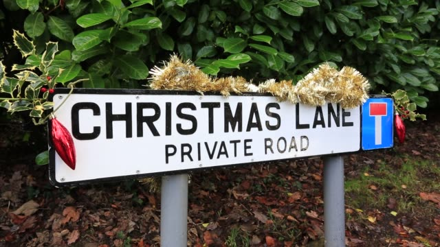 christmas lane road sign decorated with baubles, holly and tinsel, cumbria, uk. - lametta stock-videos und b-roll-filmmaterial