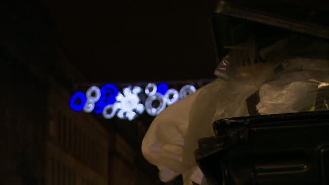 christmas lights behind bin bags in a skip - dustbin stock videos & royalty-free footage