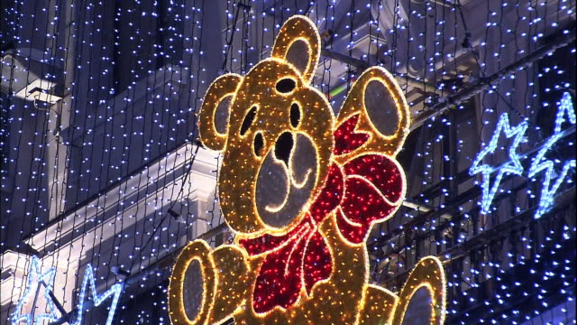 stockvideo's en b-roll-footage met christmas lights flash around a decorative bear on a department store. - teddybeer