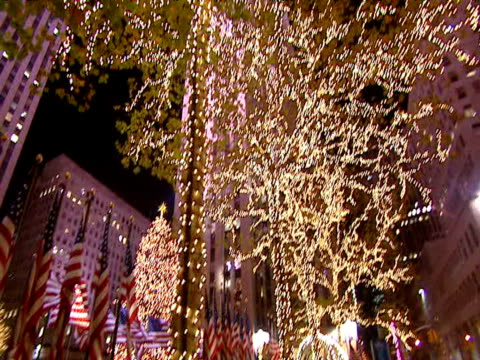 christmas lights in trees tilt and pan down to stars and stripes on line of flagpoles with rockefeller center and large christmas tree in background - rockefeller center christmas tree stock videos & royalty-free footage