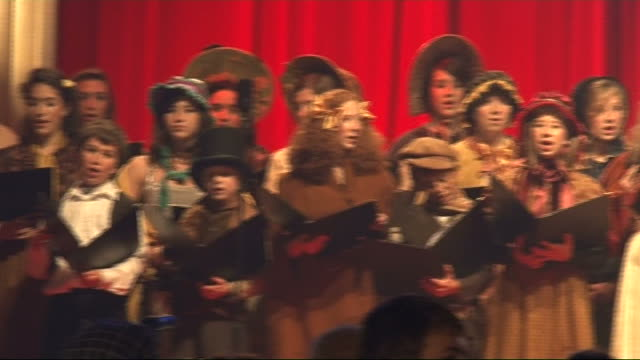 'A Christmas Carol' premiere AT Carol singers in costume singing / Andre Bocelli onto stage