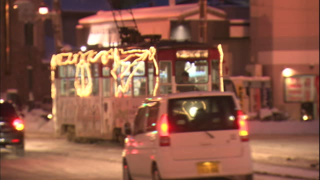 Christmas lights shine on a street car moving along a snowy street in Hakodate, Japan.