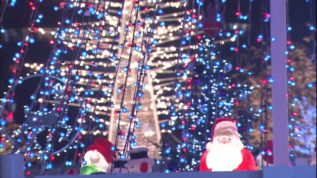 Christmas lights twinkle around illuminated Santa Claus statues during the Sapporo White Illumination ceremony in Japan.