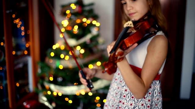 christmas. little girl preparing the violin to start playing. - 10歳から11歳点の映像素材/bロール
