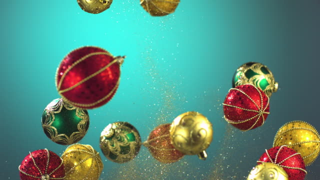 vídeos de stock, filmes e b-roll de christmas ornaments thrown into green background with gold glitter, slow motion - ornament