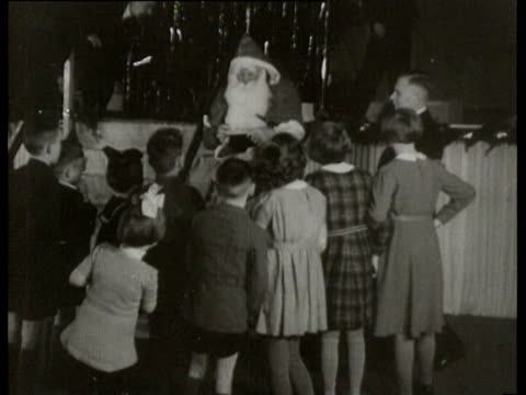 a christmas party for wounded german soldiers german orphan childs and offcials a santa claus hands out presents to children and seyssinquart joins in - orphan stock videos and b-roll footage