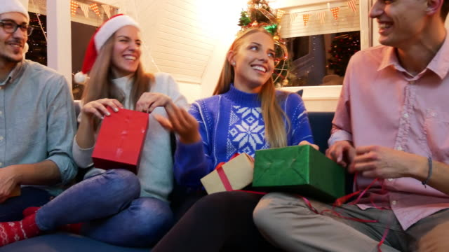 christmas party -  generation z celebrating christmas and opening christmas gifts - unwrapping stock videos & royalty-free footage
