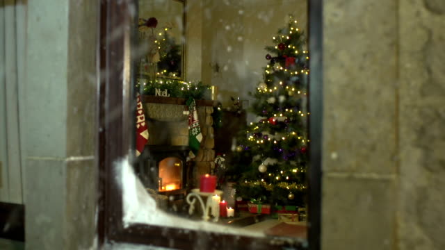 christmas scene through window with snow falling outside - christmas stocking stock videos and b-roll footage
