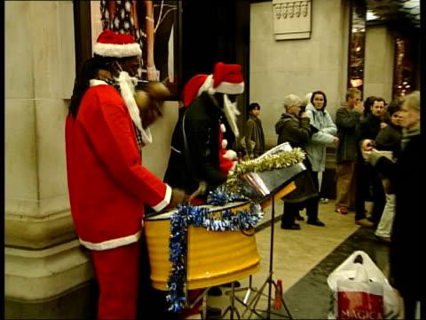 last minute rush; itn england: london: oxford street int steel band playing in shopping arcade night gv christmas lights and traffic on busy oxford... - オックスフォードシャー点の映像素材/bロール