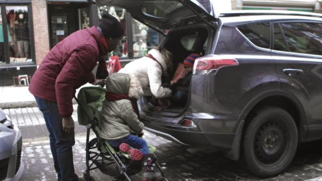 vídeos de stock e filmes b-roll de christmas shopping mix race family loading car of bags of presents - miscigenado