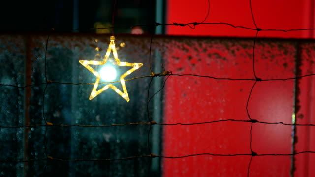 Christmas star ornament hangs on fence