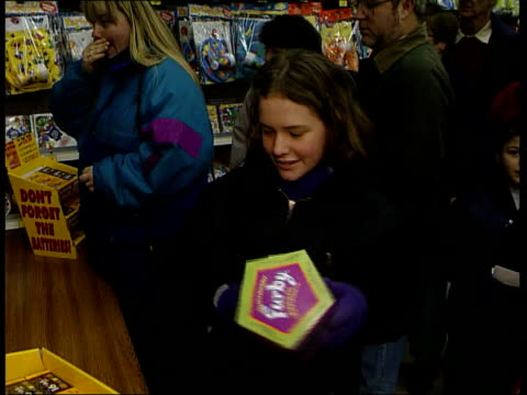 london parents towards along toy store aisle pan as join queue for 'furby' shop assistant handing customers furby toys at counter gv furby display... - cute stock videos & royalty-free footage