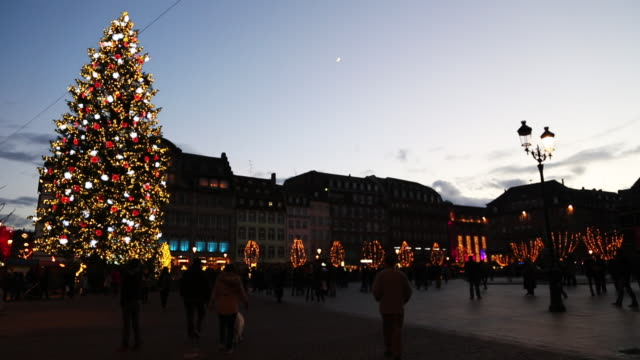 A Christmas tree and a small crescent moon near generic town square