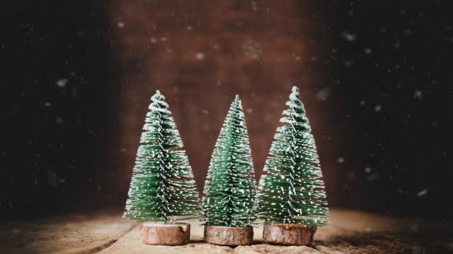 julgran och snö faller på grunge bord av trä och mörka bruna trä wall.winter holiday gratulationskort - mall bildbanksvideor och videomaterial från bakom kulisserna
