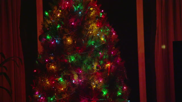 vidéos et rushes de medium tilt down christmas tree decorated with colored lights in front of window at night and gifts underneath - cadeau de noël