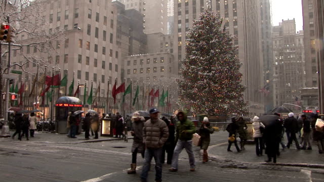 christmas tree lit up at rockefeller center during snowstorm as pedestrians walk by. - rockefeller center christmas tree stock videos & royalty-free footage