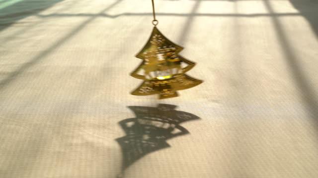 背景に太陽光から影で揺れるクリスマスツリー装飾真鍮 - 真鋳点の映像素材/bロール