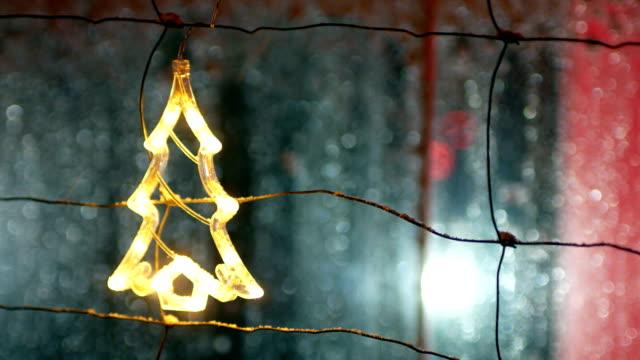 Christmas tree ornament hangs on fence