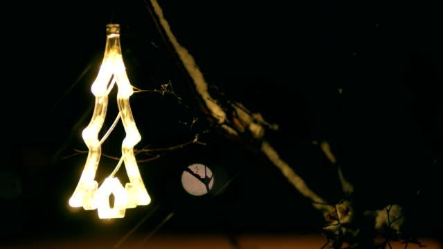 Christmas tree ornament hangs on tree branch