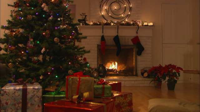 vidéos et rushes de ms, christmas tree surrounded with presents in decorated living room with fireplace - noël