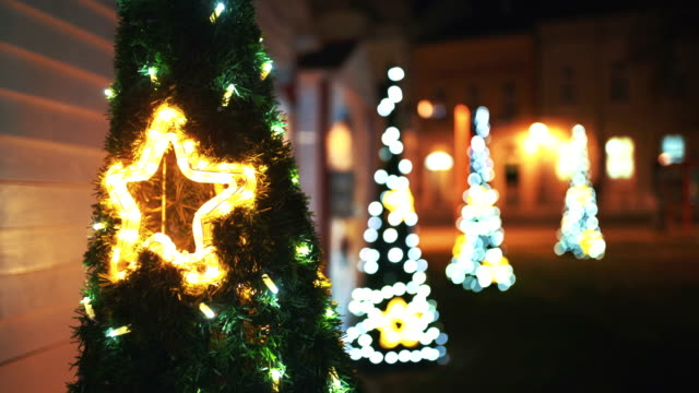christmas trees in the street at night. - courtyard stock videos & royalty-free footage