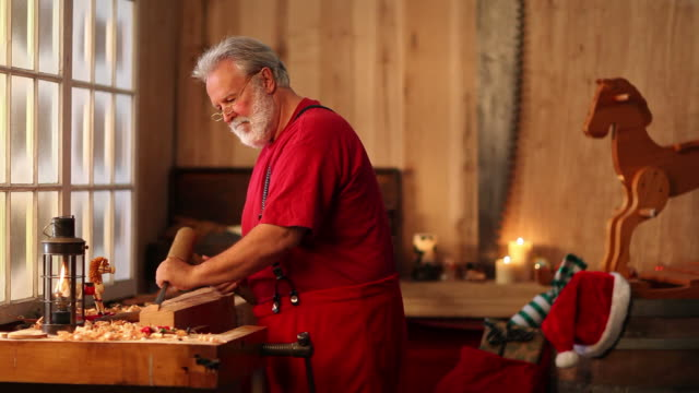christmas video of santa claus making a toy in workshop - north pole stock videos & royalty-free footage