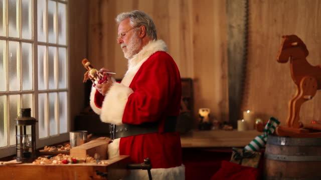 video di natale, babbo natale dipinto di giocattoli in north pole workshop - sacca video stock e b–roll