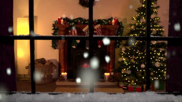 4K Christmas window scene. Snowing outside. Warm fire inside
