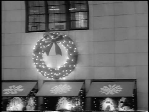stockvideo's en b-roll-footage met b/w 1963 christmas wreath with lights above awnings of store / nyc / newsreel - kleine groep dingen
