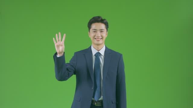 vídeos de stock e filmes b-roll de chroma key - businessman indicating number 4 by gesturing - número 4
