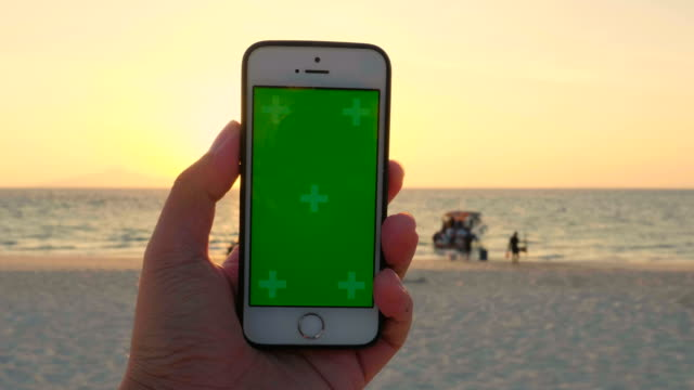 vídeos de stock e filmes b-roll de chroma key handheld smartphone on the beach - billboard