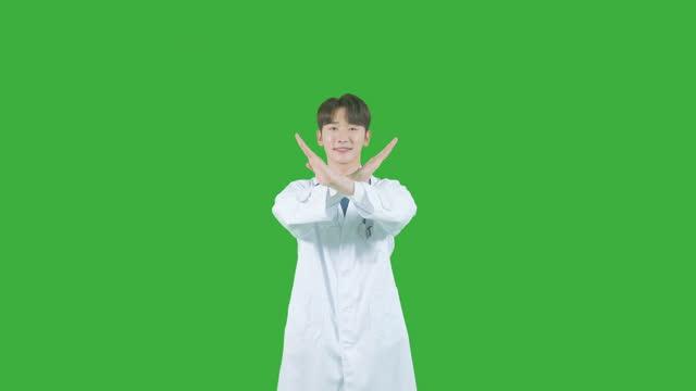 vídeos y material grabado en eventos de stock de chroma key - male doctor looking forward and making x sign with his hands - letra x